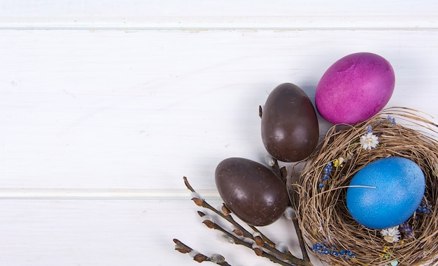 Fundo colorido com ovos de páscoa no fundo branco da placa de madeira.