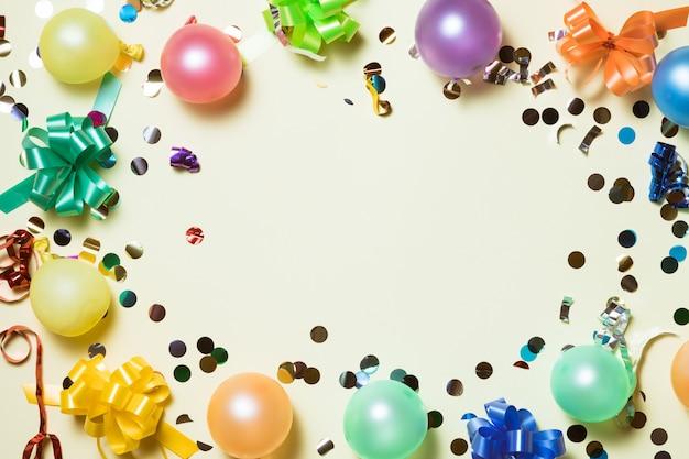 Fundo colorido de festa de aniversário com chapéus de festa e confetes em fundo amarelo