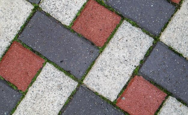 Fundo colorido e textura de novas lajes de pavimentação. a textura dos ladrilhos pavimentados é vermelha e cinza. fundo do piso de pedra quadrada do tijolo de cimento. lajes de pavimentação de concreto.