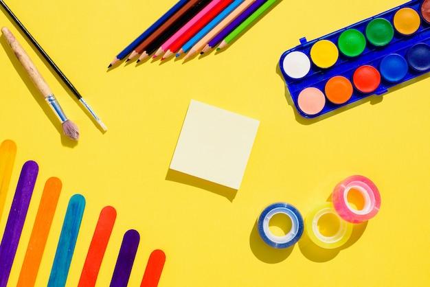 Fundo colorido liso leigo com material de artesanato no caminho de volta para a escola.