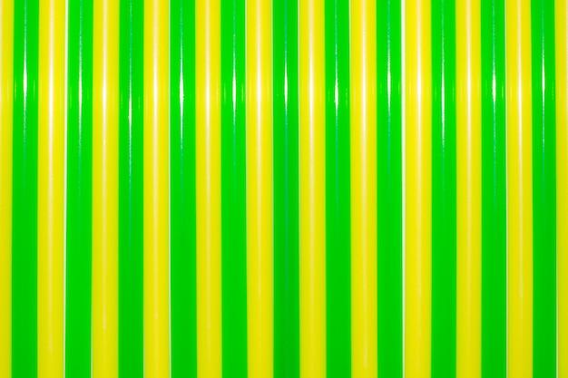 Fundo colorido. palhas bebendo coloridas do cocktail do plástico. backg verde e amarelo