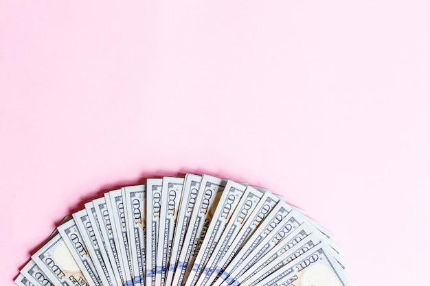 Fundo com as notas de dólar do americano cem do dinheiro do dinheiro isoladas no rosa. lay plana. vista do topo