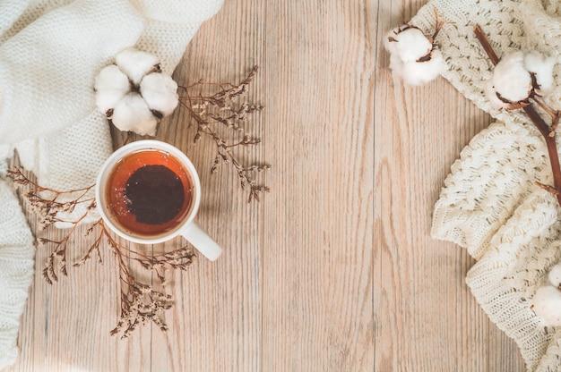 Fundo com blusas quentes e xícara de chá. ainda vida aconchegante em tons quentes. conceito de outono-inverno.