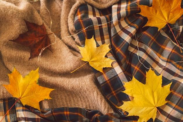 Fundo com blusas quentes roupas de malha com folhas de outono amarelas fundo quente