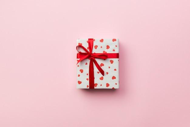 Fundo com caixa de presente e corações no fundo cor-de-rosa. vista superior com espaço de cópia para texto