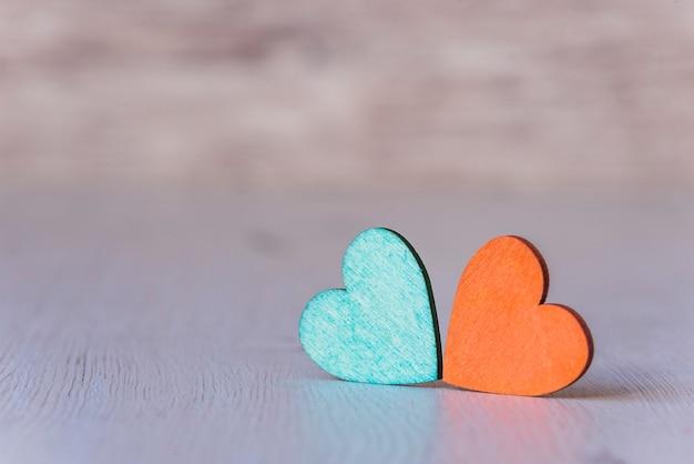 Fundo com dois corações verdes e laranja, em fundo de madeira