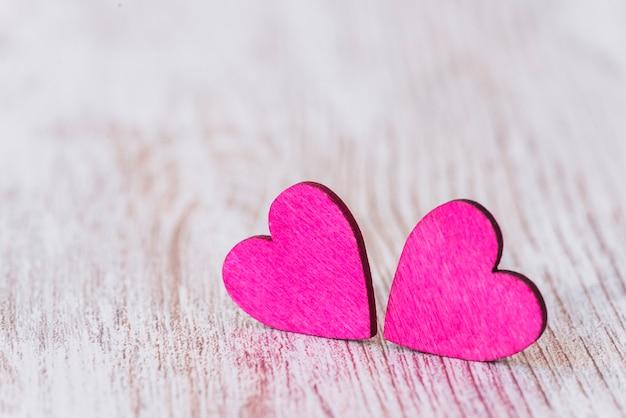 Fundo com dois corações vermelhos em fundo de madeira