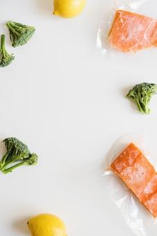 Fundo com filé de salmão congelado embalado em sacos plásticos, limões frescos e florzinhas de brócolis