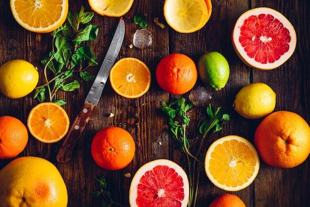 Fundo com frutas cítricas fatiadas, hortelã e faca