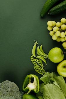 Fundo com frutas e legumes frescos na superfície da mesa verde, vista de cima