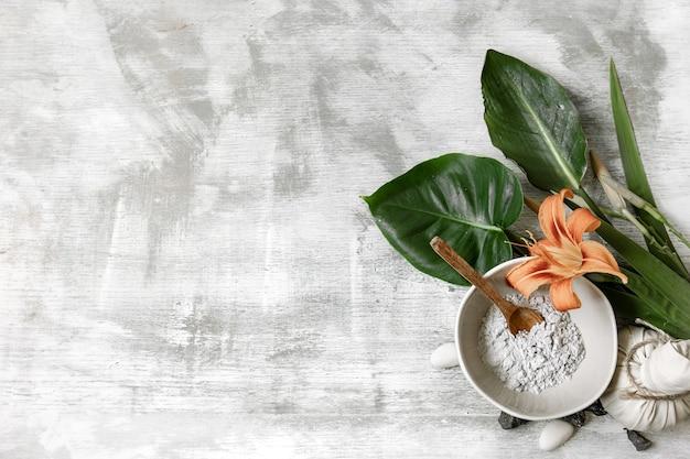 Fundo com ingredientes naturais na consistência de pó para o preparo de uma máscara para o cuidado da pele.