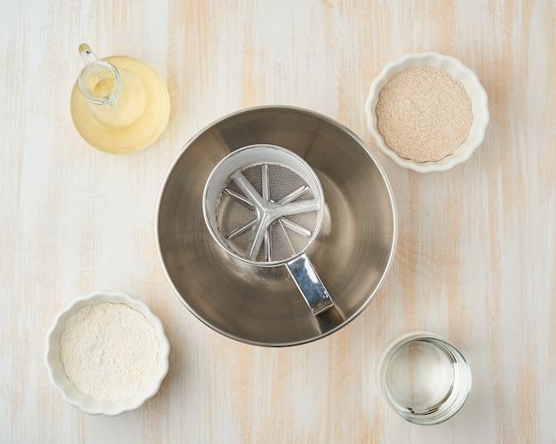 Fundo com ingredientes para massa, tigela e peneira.