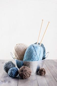 Fundo com lã e agulhas de tricô na mesa de madeira