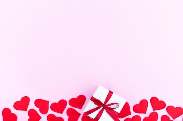Fundo com presente e corações com espaço livre para texto em fundo rosa pastel. camada plana, vista superior. conceito de dia dos namorados. conceito de dia das mães.