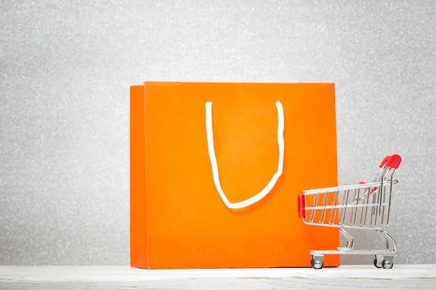 Fundo com saco de compras colorido e carrinho de compras. conceito de desconto.