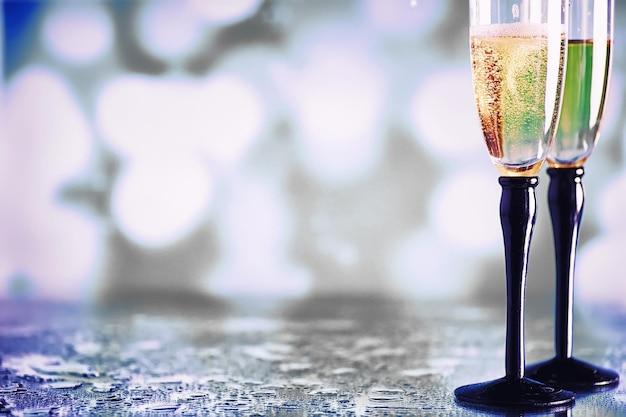 Fundo com taças altas para vinhos espumantes. champanhe e spray em taças de vidro. bebida comemorativa com reflexão.