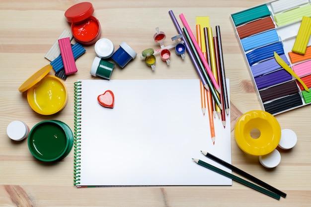 Fundo com tintas, marcadores e uma folha de papel em branco