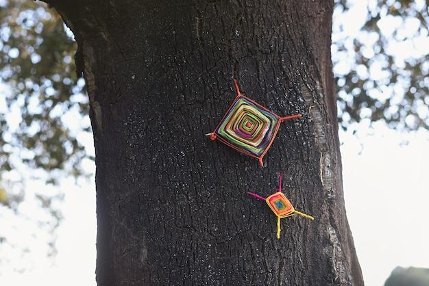 Fundo com tronco de árvore decorado com mandalas de lã trançada