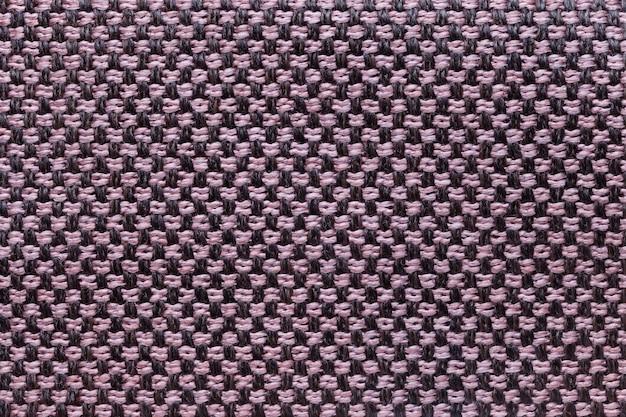 Fundo cor-de-rosa e preto de matéria têxtil com projeto da xadrez, close up. estrutura da macro de malha.
