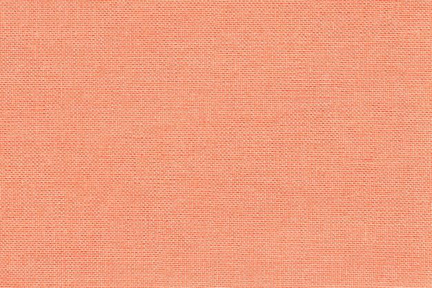 Fundo coral claro de um material de matéria têxtil com teste padrão de vime, close up.