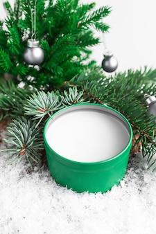 Fundo cosmético de natal com remédio para o corpo em uma jarra verde na neve closeup