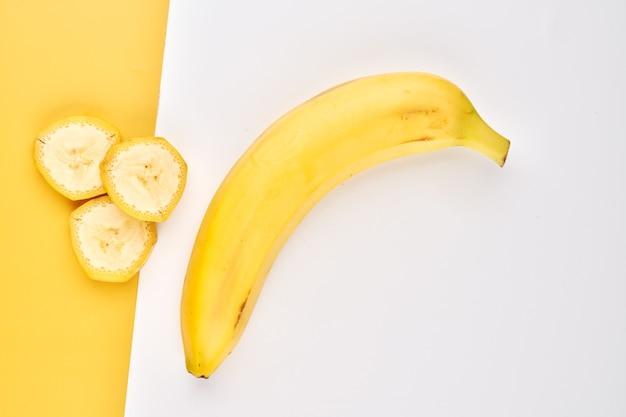Fundo criativo de banana. pano de fundo amarelo e branco com bananas inteiras, descascadas e fatiadas