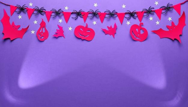 Fundo criativo de halloween em roxo, vermelho e preto, plana leigos, imagem panorâmica com cópia-espaço. projectores, figuras artesanais de papel de morcegos e abóboras de lanterna de jack, guirlanda com bandeiras e aranhas.