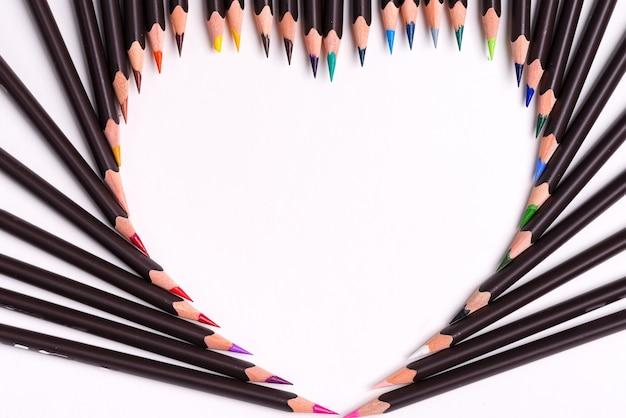Fundo criativo de lápis coloridos em forma de coração em um fundo branco. postura plana.