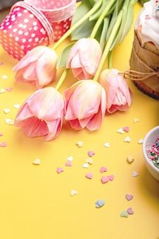 Fundo criativo do feriado da páscoa com bolo de páscoa, tulipas e decorações vista superior plana leigos com espaço de cópia