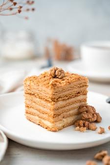 Fundo culinário, bolo de mel com nozes em um fundo de luz suave. vista lateral, close-up.