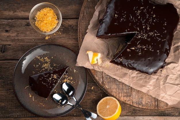 Fundo culinário com bolo de chocolate com limão e raspas em um fundo de madeira.