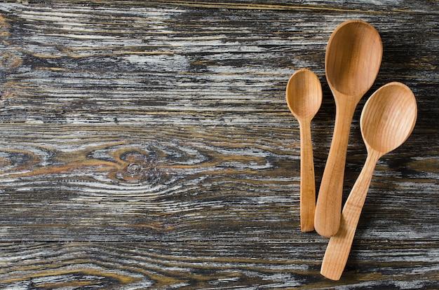 Fundo culinário com colheres rústicas na mesa de madeira vintage.