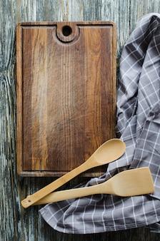 Fundo culinário com utensílios de cozinha rústico na mesa de madeira vintage.