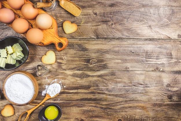 Fundo culinário de cozimento do dia dos namorados. ingredientes para cozinhar na mesa da cozinha de madeira, receita de pastelaria de cozimento. cookies de forma de coração. vista do topo. postura plana.