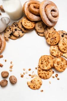 Fundo culinário de loja caseira, espaço livre de vista superior. scones integrais e pãezinhos assados em círculo perto de garrafas de leite na mesa branca. conceito de delicioso café da manhã
