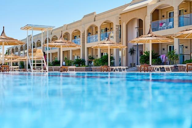Fundo da água na piscina azul, superfície da água com um reflexo do sol