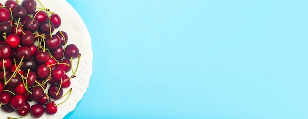 Fundo da bandeira cereja. cereja doce suculenta vermelha em um prato branco sobre um fundo azul claro. bagas suculentas frescas de verão e conceito de comida. foto de alta qualidade