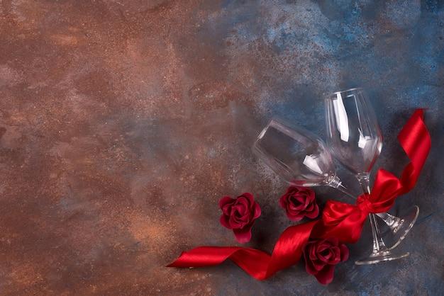 Fundo da celebração do dia dos namorados com dois copos, rosas e fita vermelha