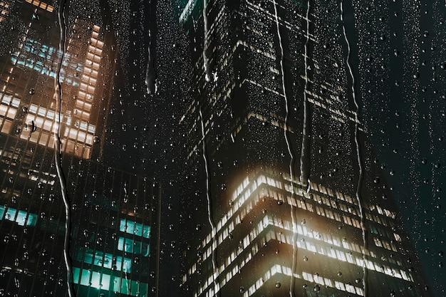 Fundo da cidade à noite, janela chuvosa com prédios de escritórios, textura de água