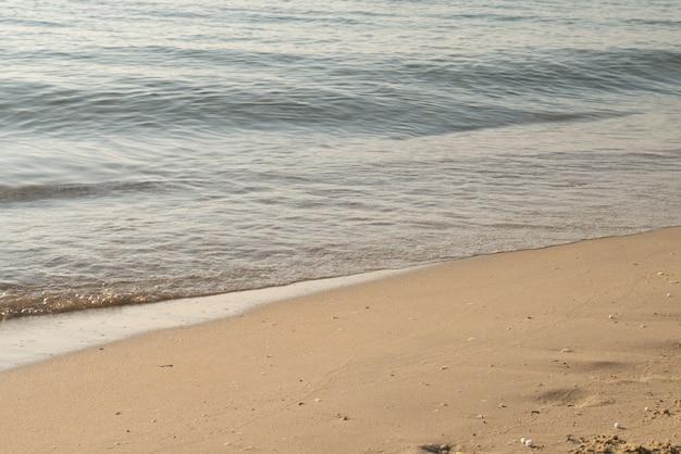 Fundo da natureza da onda da praia do litoral e da areia do litoral com superfície da água da luz solar para o conceito do estilo de vida do abrandamento do feriado