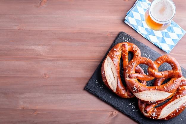 Fundo da oktoberfest com cerveja, pretzels e decoração tradicional da baviera, close-up no tampo da mesa de madeira, copie o espaço