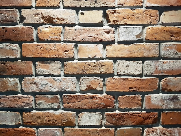 Fundo da parede de tijolo vermelho textura do close up dos blocos de pedra vermelha
