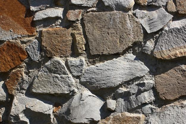 Fundo da parede pavimentado com pedras de diferentes formas irregulares na argamassa de cimento.