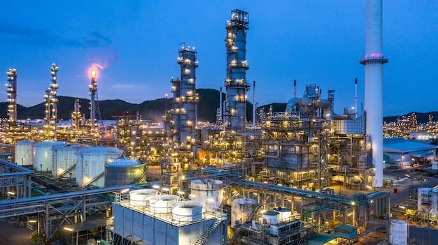 Fundo da planta de refinaria de petroquímica e de óleo da vista aérea na noite, planta de fábrica petroquímica da refinaria de petróleo na noite.