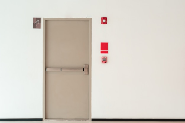 Fundo da porta de saída de emergência com a parede do espaço da cópia, prédio de escritórios interior
