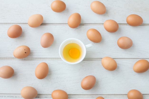 Fundo da textura da mesa de cozinha com o ovo amarelo fresco da gema no copo branco. vista do topo t