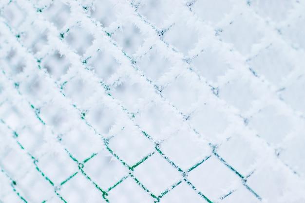 Fundo da textura da neve do inverno feito da malha do metal coberta com a geada da neve. cerca congelada