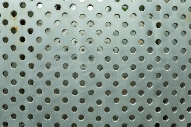 Fundo da textura do metal com muitos furos.