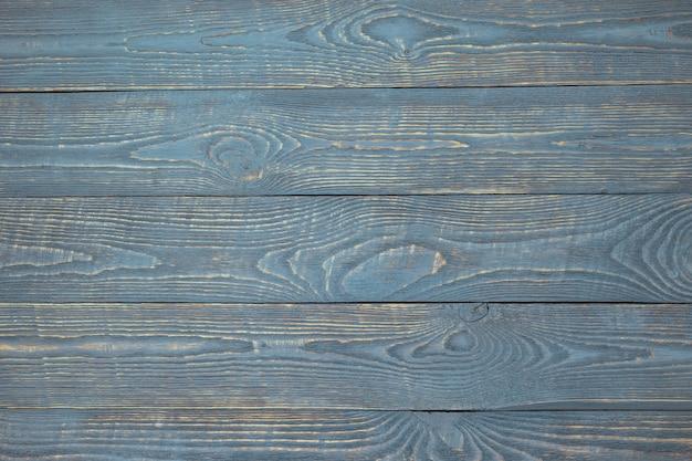 Fundo das placas de madeira da textura com os restos da luz - pintura azul. horizontal.