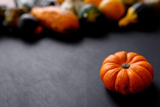 Fundo de ação de graças de abóbora de outono - abóboras laranja sobre mesa preta